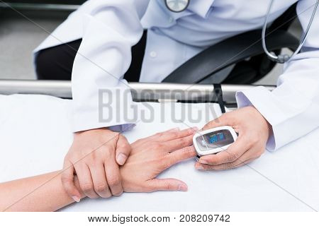 Doctor measuring blood oxygen levels of the sleeping elder patient on bed with oximeter.