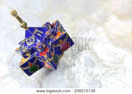 Enameled blue star shaped Hanukkah dreidel on a soft white background