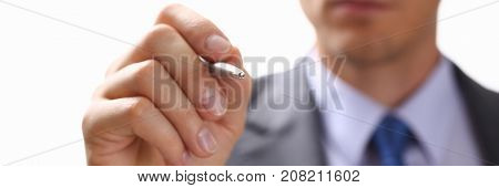 Male arm in suit and tie point in camera tip of silver pen closeup. Sign gesture, read pact, sale agent, bank job, make note, loan credit mortgage investment, finance chief, legal law concept