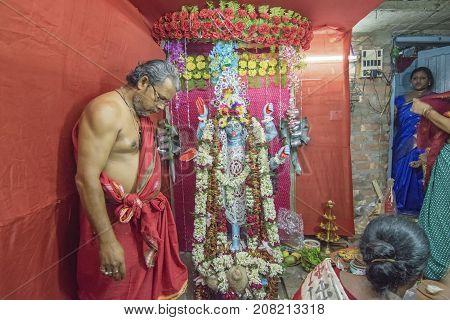 KOLKATA INDIA - JUNE 17 2017 - Hindu priest worshipping Goddess Kali at night during Kali Puja Hindu festival of Deepavali or Diwali. Celebtated all over India. Shot under mixed light.
