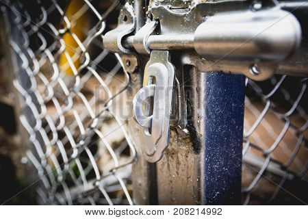 Door latches with an old metal fence net door.