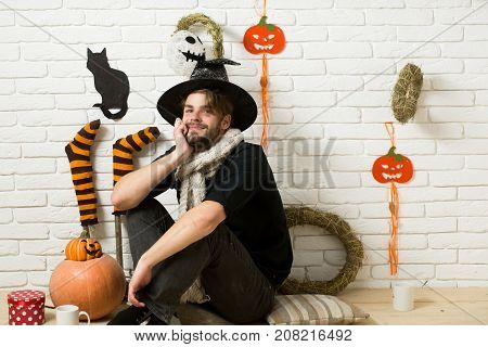 Halloween man smiling in witch hat. Macho sitting with gift box and cups on floor. Pumpkins stockings black cat wreaths mummy on brick wall. Happy holiday celebration. Present and surprise concept