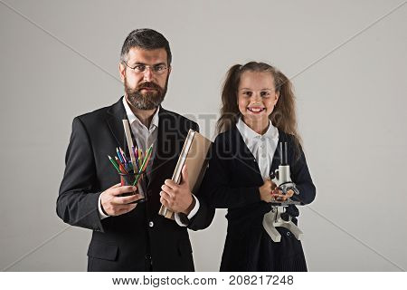 Kid And Tutor Hold Book, Pencils And Microscope