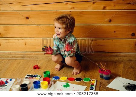 Child happy smiling with colored hands gouache paints and drawings. Boy painter painting on wooden floor. Imagination creativity and freedom concept. Arts and crafts. Kid learning and playing.
