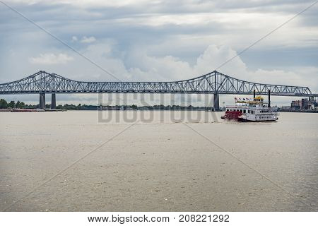 bridge over the Mississippi river with a boat in New Orleans LA