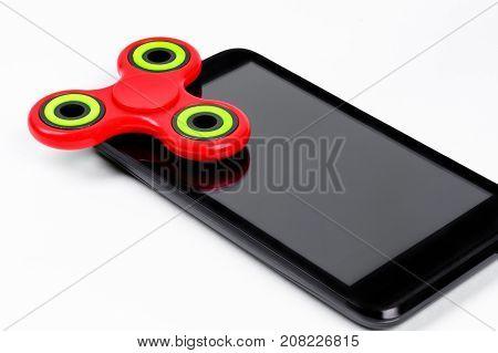 Red fidget spinner lying on smartphone. White background