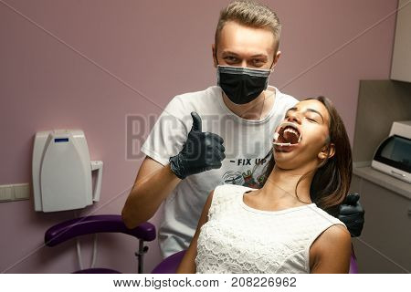 Female patient with dental dilator in her mouth on reception at doctor in dental office.