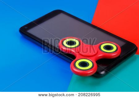 Red fidget spinner lying on smartphone. Multicolored background
