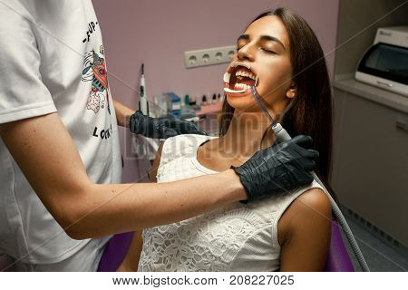 Dentist treats teeth of young woman using dental tool and mouth dilator. Close up.