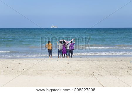 Uppuveli, Sri Lanka - March 26 2017: Local Girls With A Sarong Cloth In Their Hands At The Beach