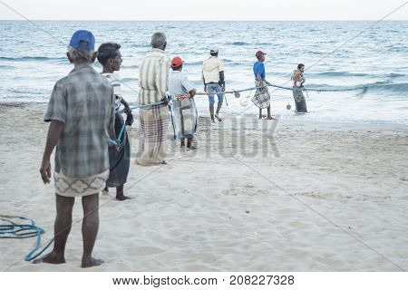 Uppuveli, Sri Lanka - March 26 2017: Local Fishermen Pulling At The Rope Of The Fishernet At The Bea