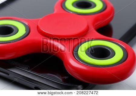 Macro shot of red fidget spinner lying on smartphone. Selective focus