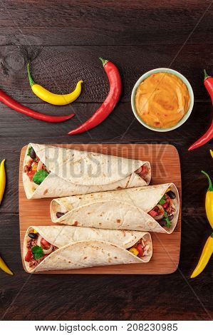An overhead vertical photo of Mexican burritos with beef, rice, black beans, and vegetables, with a cheese sauce, chili peppers, and a place for text, shot from above on dark wooden rustic textures