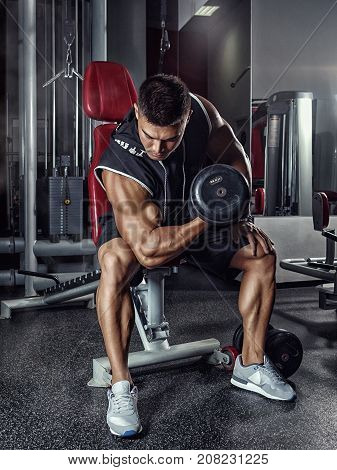 Muscular bodybuilder sitting on a bench in the gym coaches the biceps lifting the dumbbell