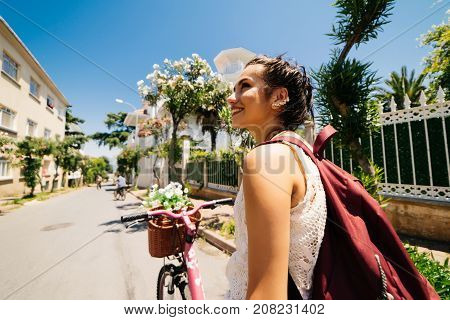 Smiling eastern girl on vintage bicycle with backet of flowers