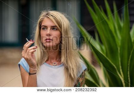 Beautiful blonde girl smokes a cigarette. Women's hands with a tattoo. Urban fashion.