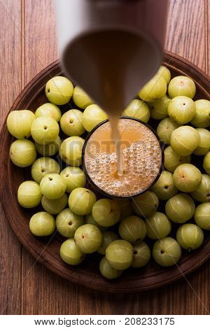 Indian fresh gooseberry juice or stock photo of Amla juice (Phyllanthus emblica) , selective focus