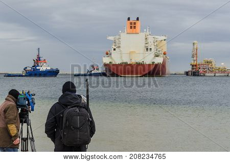 CAMERAMAN AND LNG TERMINAL - Reporters in a maritime port