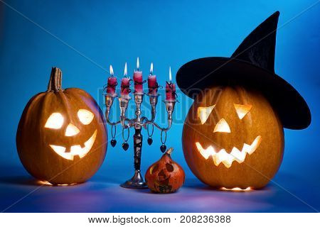 Halloween pumpkin with a candlestick funny face face on a blue background