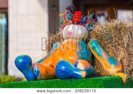 The figure of a seated wizard assembled from pumpkins is located in the street around the sheaves of hay. Colorful autumn in Moscow city, Russia.