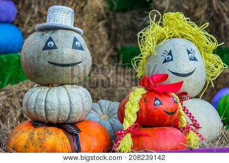 The figure of a family from mom dad and daughter with braids assembled from pumpkins is located in the street around the sheaves of hay. Colorful autumn in Moscow city, Russia.