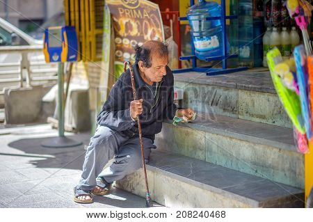 Iran Tehran 2016 - beggar begging alms on the steps of the store