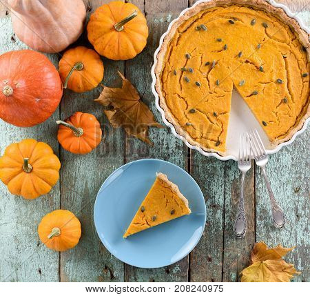 Homemade American pumpkin pie with pumpkin seeds decorated with bright orange pumpkins on shabby robin egg blue background above view