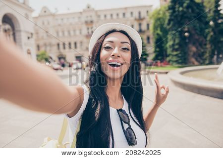 Cute Lady With Bronze Skin And Long Dark Hair, In Cap Is Making A Selfie Shot While Outside In Town.