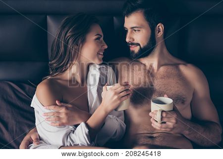 Enjoy Each Other, Mug Of Tea. Two Lovers Are Cuddling In The Bed, Looking Deep Into Eyes Of Each Oth