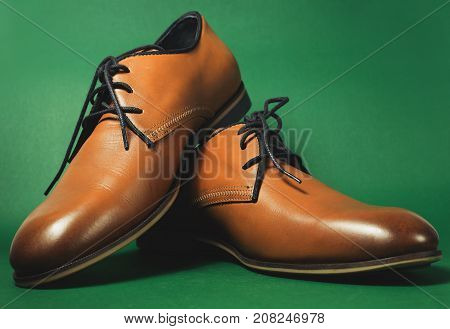 Brown shoes isolated on the green background