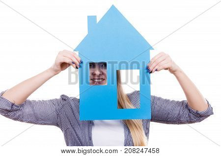 Dream about stabilization and family. Blonde girl holding blue paper house model cutout. New flat apartment. Isolated on white