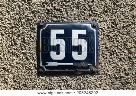 Weathered grunge square metal enameled plate of number of street address with number 55 closeup