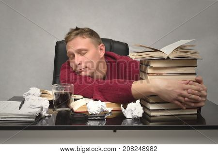 Student man tired of studying and sleeping on the school desk table with books and crumpled paper pages around. Tired worker. Overworked businessman.