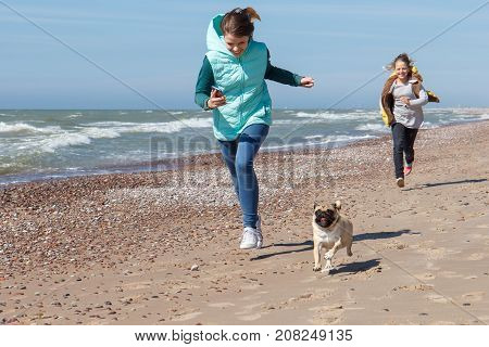 two young girls run along the sea with the dog