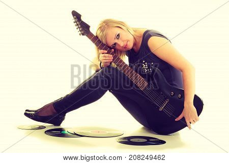 Music retro style. Young rock roll female star holds playing electric guitar surrounded by vinyl record. Classical audio collection.