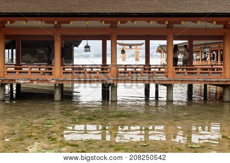 Miyajima, Japan - September 14 2017: Itsukushima Shrine With Torii Gate And Watching Tourists