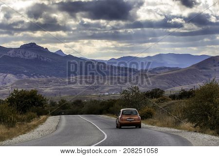 The red car travels along the highway around a beautiful landscape. Bluish thunderous mountains under the sky covered with clouds