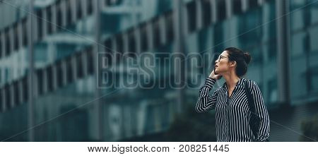 Businesswoman Walking Outdoors And Talking On Mobile Phone