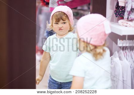 Adorable toddler girl in baby apparel store buying warm autumn clothes fiting knitted hat disappointed dace.