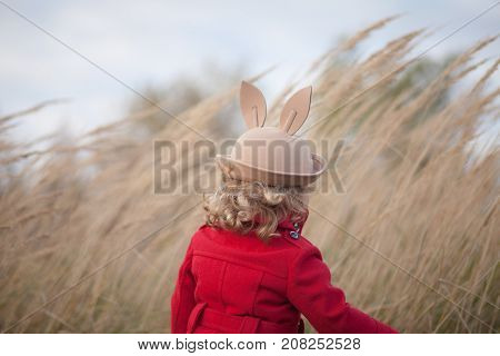 Toddler girl walking alone in the autumn field wearing red coat and felt hat with binny ears. Cold blowy windy weather sad mood strong wind.