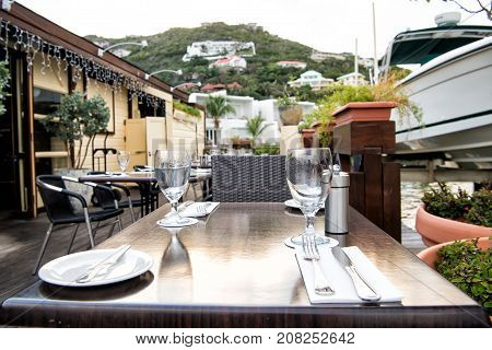 Table and chairs on restaurant terrace on natural background in Philipsburg Sint Maarten. Glasses and cutlery. Drinking and dining outdoors. Summer vacation and holidays. Enjoy life concept.