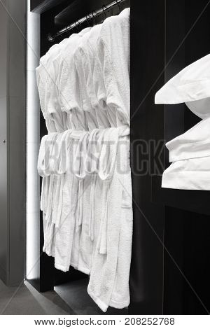 white bathrobes pillows towels hanging in wooden closet of service room in hotel