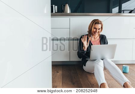 Woman on video call using a laptop computer sitting on kitchen floor wearing earphones. Smiling woman sitting on floor with a coffee mug making gestures on a video call.