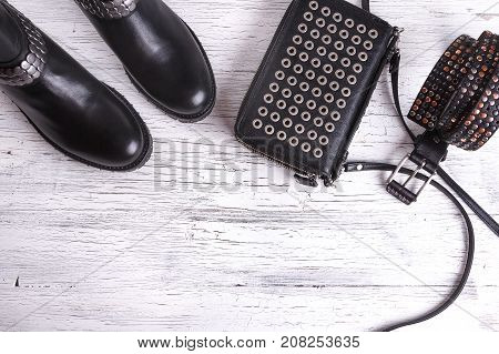 Women's black leather handbag on wooden floor next to leather belt and boots on wooden background