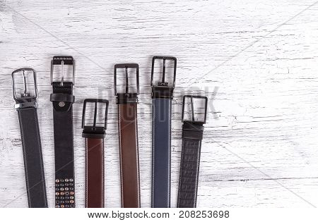 Men's and women's belts. Leather belts different colours on a white wooden background.