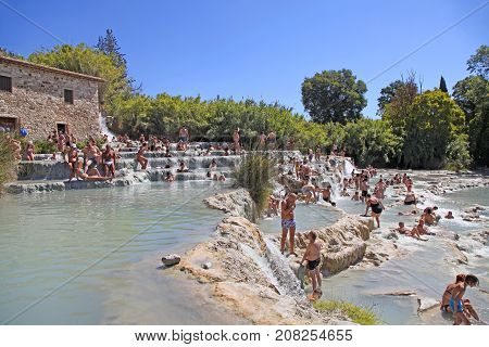 SATURNIA, ITALY - JULY 26, 2017: Tourists swimming and relaxing in hot springs at Cascate del Mulino in Saturnia, Grosseto, Tuscany, Italy. This world famous natural spa has natural waterfalls and hot springs.