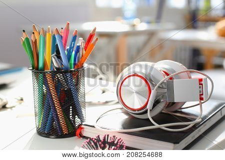 Headphones diary and pencil lie on the desk of the concept of remote distance education listen to music compose tunes for sale school sound training instruments thematic studing sound recording studio