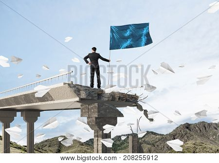Rear view of confident businessman in suit holding flag in hand while standing among flying paper planes on broken bridge with cloudly skyscape on background. 3D rendering.