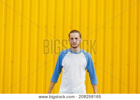 Peaceful and concentrated student guy with stylish haircut standing with a neutral expression on a yellow wall background. Copy space.