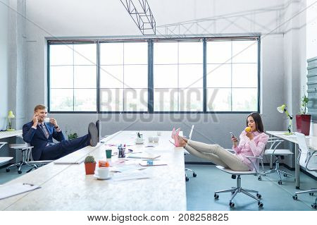 Young employees, lunch break, put their feet on the table. A girl is eating an apple and looking into the phone. A man is talking on the phone and drinking coffee.